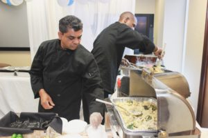 Two catering workers preparing for a meal