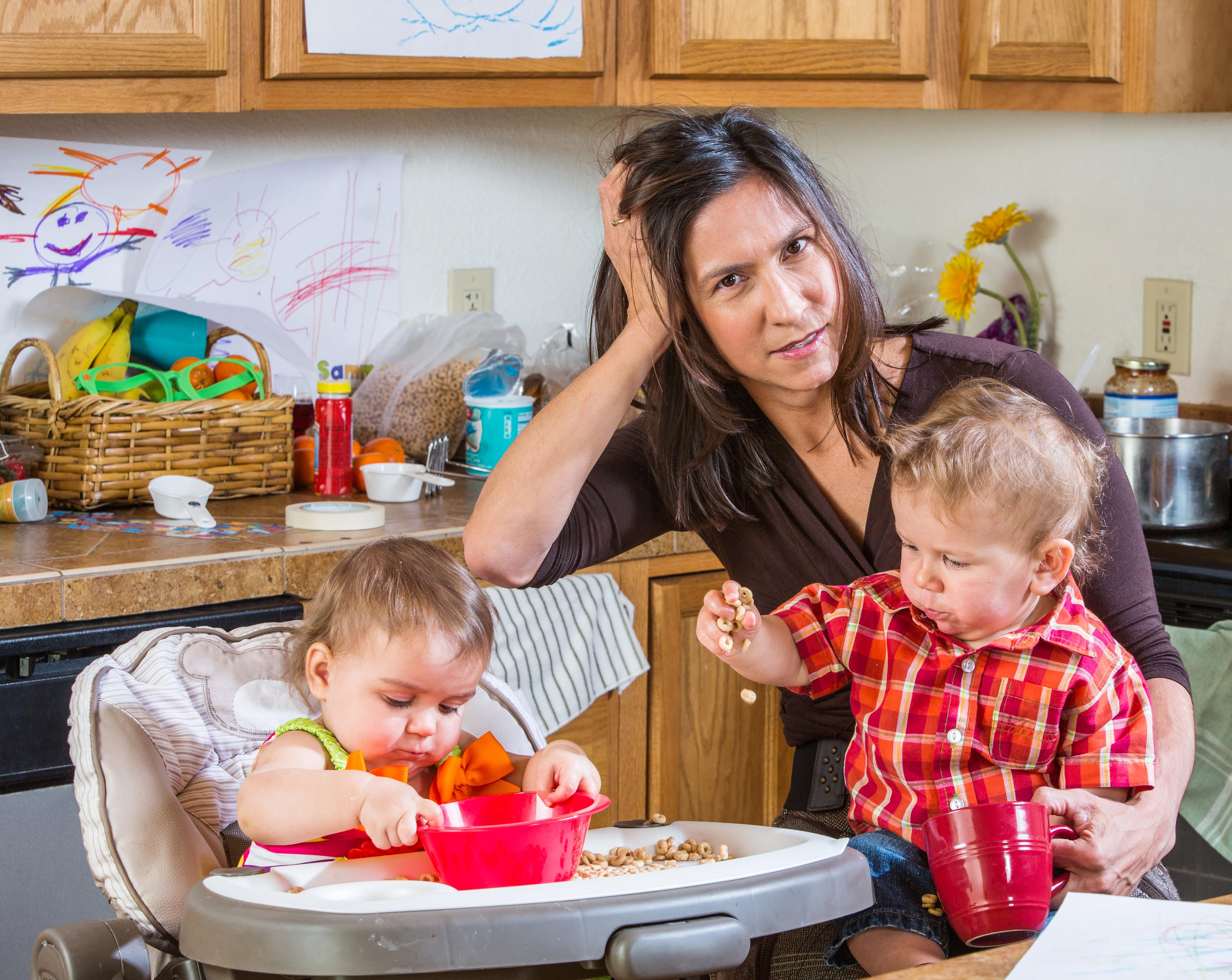 A mother of two toddlers stresses over her messy kitchen.
