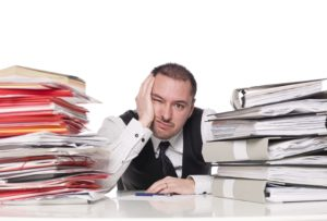 A frustrated businessman seated at a cluttered desk