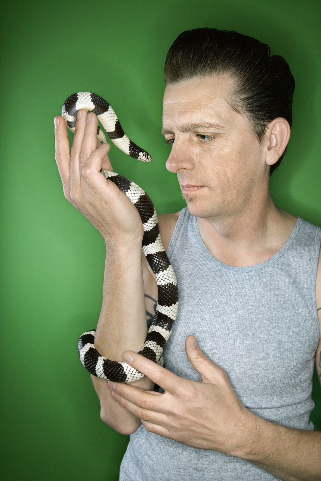 A man lovingly holds up the pet snake he is unable to store in a storage unit