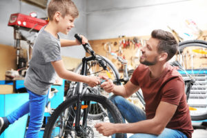 Dad and young son clean and prepare a bicycle for storage over the winter