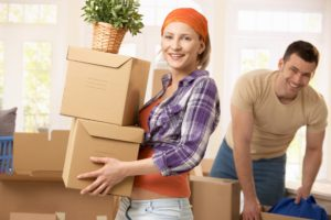 A young couple moves boxes into their new home after completing a moving day checklist