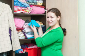A young woman organizes her wardrobe for a more organized New Year