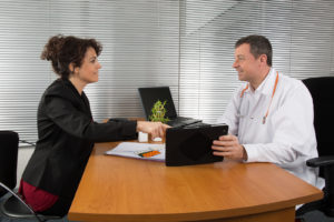 A pharmaceutical sales representative showing products to a doctor