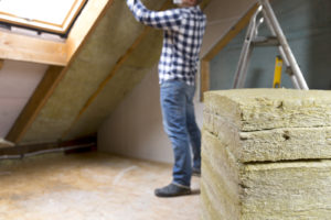 A man renovating attic space installs insulation into the ceiling