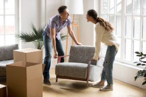 A young couple moving furniture