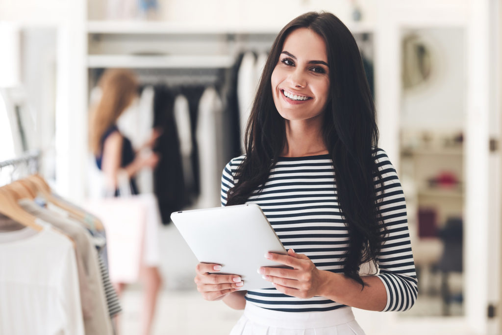 woman smiling inside of clothing boutique