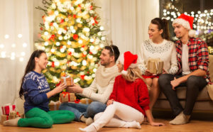 A family gathers by a Christmas tree with gifts