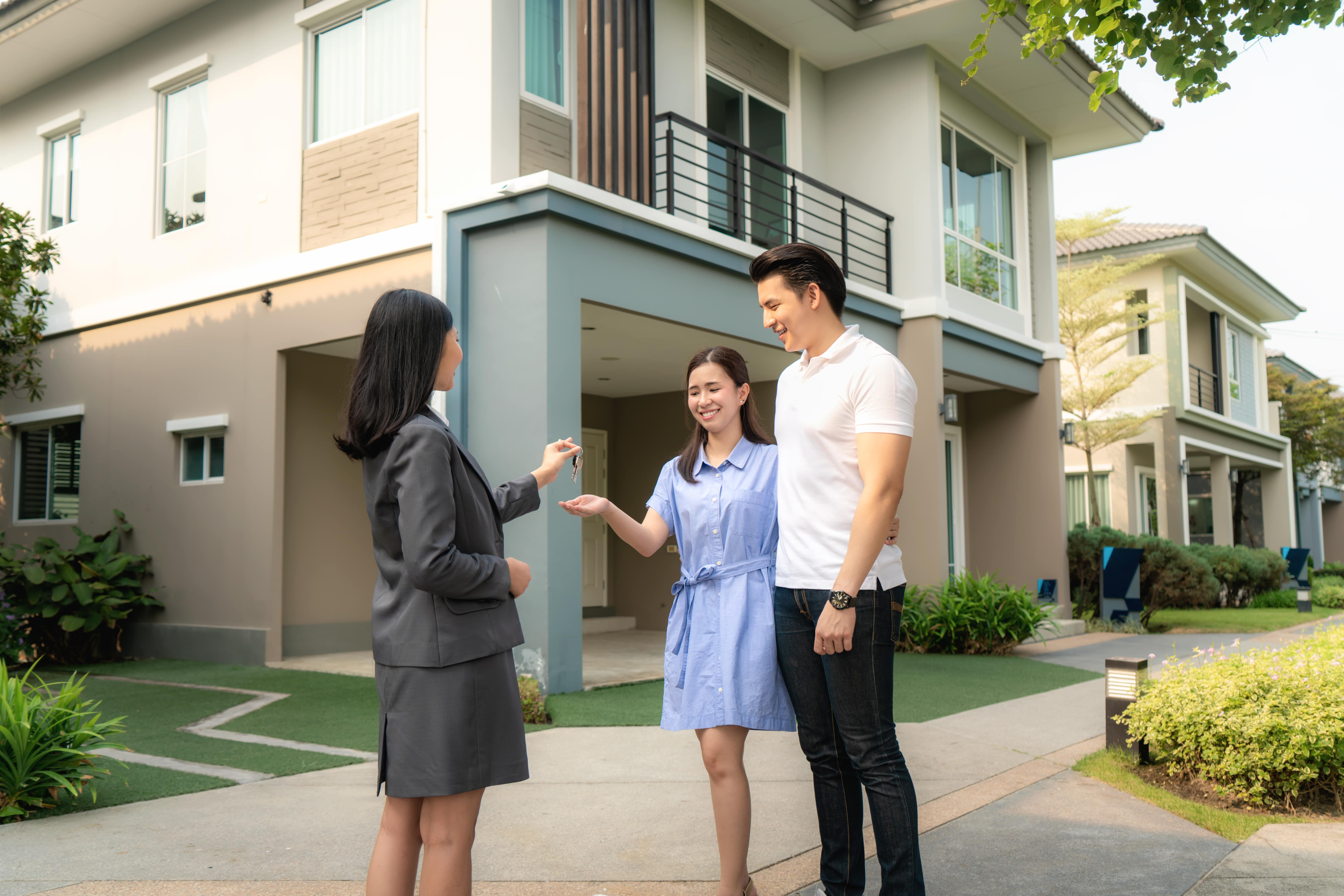 A young couple getting the keys to their new home with the help of their real estate agent.